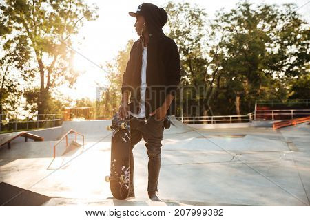 Young african man skateboarder standing with a skateboard at sunset city park