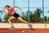 Runner sprinting towards success on run path running athletic track. Goal achievement concept. Female athlete sprinter doing a fast sprint for competition on red lane at an outdoor field stadium. poster