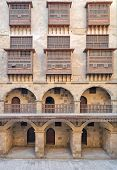 Facade of caravansary (Wikala) of Bazaraa with vaulted arcades and windows covered by interleaved wooden grids (mashrabiyya) suited in Tombakshia street Al Gamalia district Medieval Cairo Egypt poster