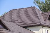 Brown corrugated metal profile roof. The roof of corrugated sheet. Roofing of metal profile wavy shape. poster
