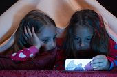 Children and technology concept. Girls with involved faces. Girl friends under blanket playing with mobile phone. Pyjamas party for children. Kids wearing red jammies in bed on black background. poster