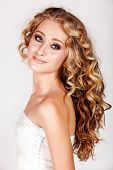 Beautiful young blonde woman with long curly hair in white fashion sequin top isolated on white background. poster