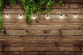 Garland lamps over wooden board fence with green leaves. Decoration background