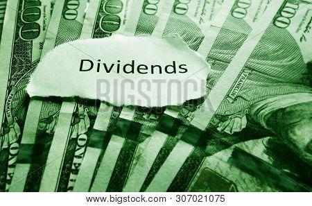 Dividends paper message on hundred dollar bills - stock market concept poster