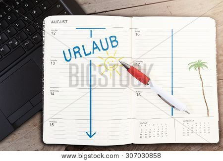 Top View Of Calendar On Table With Word Urlaub, German For Vacation, And Sun Icon Against Wooden Tab
