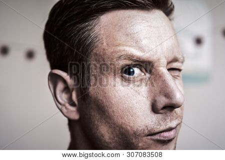 Serious But Inquisitive Looking Man Looking Directly At Camera