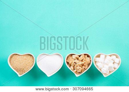 Top View Of Various Types Of Sugar. Cube Sugar, Raw Sugar Brown Sugar And Granulated Sugar In Heart