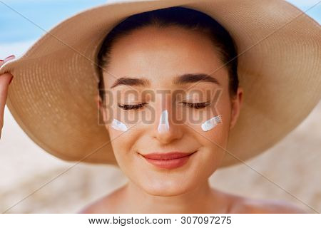 Beautiful Woman Applying Cream Sunscreen On Tanned Face. Sunscreen. Skin And Body Care. The Girl Use