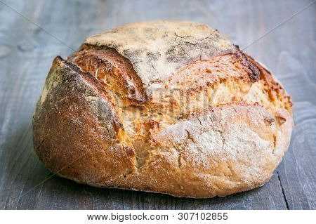 Loafs (or miche) of French sourdough, called as well as Pain de campagne, on display on a wooden table. Pain de Campagne is a typical French huge loaf of bread abiding by the traditional codes poster