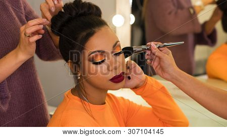 Hairstylist And Make-up Artist Makeup And Updo For Stylish Young African-american Woman In Beauty Pa