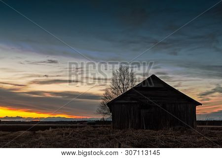 The Sun Sets Beautifully Behind An Old Barn House At The Rural Finland. The Sunset Colors The Clouds