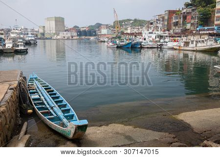 Keelung, Taiwan - September 5, 2018: Old Blue Wooden Fishing Boat Lay On Coast In Fishing Harbor Of