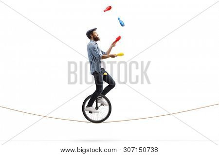 Full length profile shot of a male juggler with clubs riding a unicycle on a rope isolated on white background