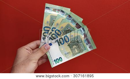 Man Holding New 100 Euro Banknotes Released On 28 May 2019. Red Background
