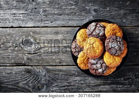 overhead view of Crinkle cookies. Cracked lemon biscuits. Chocolate biscuits, lemon crinkle cookies on a plate on a rustic wooden  table, flatlay, empty space poster