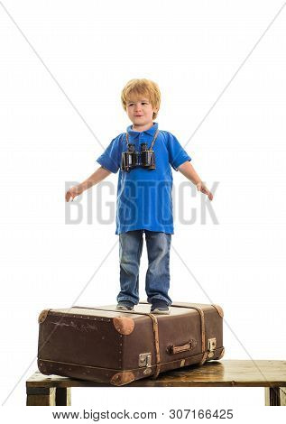 poster of Happy child boy with binoculars standing on suitcase. Dream of travel. Traveling. Vacation, travel, journey. Child boy pilot flying on suitcase. Travel suitcase. Vacation trip concept. Summer vacation