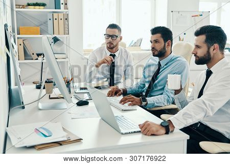 Young Business Professionals. Group Of Young Modern Men In Formalwear Working Using Computers While