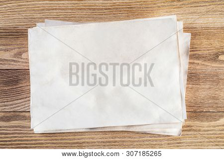 Sheet Of Paper Lying On Wooden Table. Scrapbooking And Hand Made Creativity. Rectangular Blank White
