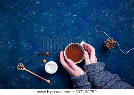 Autumn Cup Of Tea With A Spoon For Honey, A Candle, Cinnamon And Star Anise On A Dark Blue Backgroun