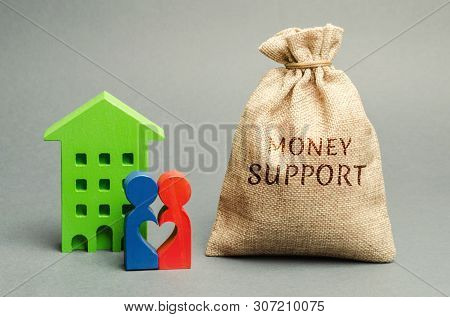 Family Standing Near The House With A Bag With The Word Money Support. Financial Assistance To Suppo
