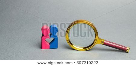 Couple Of Lovers Standing Near A Magnifying Glass. The Concept Of Finding Love And Dating Through Th