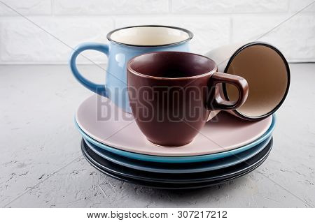 Set Of Clean Ceramic Crockery Tableware On Gray Concrete Background, Color Bowls, Plate, Cup, Dishes