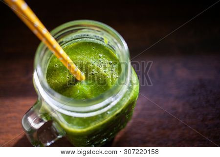 jar with green cold-pressed juice, wooden background. Healthy eating, detoxing, juicing body cleancing concept