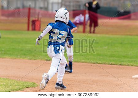 Youth Baseball Player In Blue Uniform And White Helmet Sprints Across Infield To Steal Second Base.