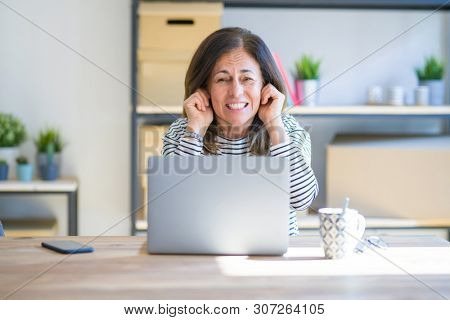 Middle age senior woman sitting at the table at home working using computer laptop covering ears with fingers with annoyed expression for the noise of loud music. Deaf concept.