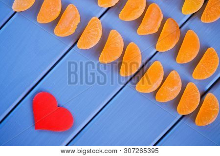 Fruit Jelly In The Form Of Mandarin Lobules Lies On The Painted Boards Next To The Heart. The Combin