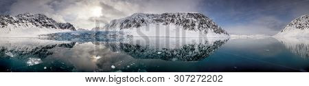 Mirror reflection panorama of the blue glacial ice, mountains and clouds of Kongsvegen glacier, in Kongsfjorden fjord, Svalbard, and archipelago between mainland Norway and the North Pole.