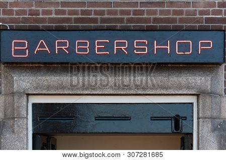Red Barbershop Neon Sign On A Brick Wall In Day Light