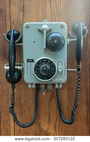 Old Phone Hanging On A Wooden Wall Close-up View