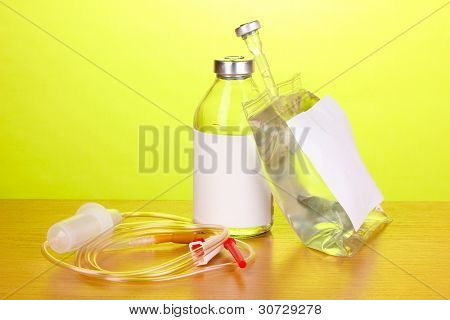 Bottle and bag of intravenous antibiotics and plastic infusion set on wooden table on green background