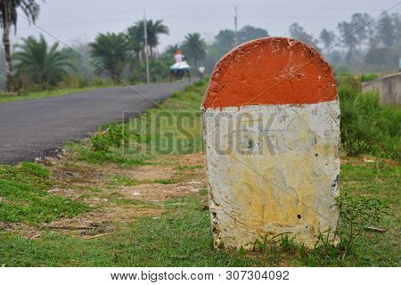 Blank Mile Stone In The Grass Near The Road, With Print Number Hundred Sign
