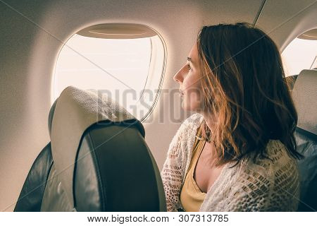 Traveler Girl Watching Through Airplane Window. Young Traveler Girl In Vacation. Girl Traveling By A