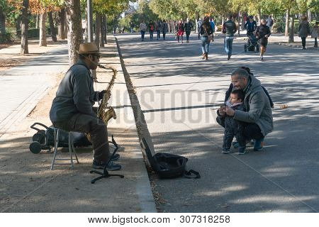 Madrid, Spain - November 12,2017 : Unidentified Father And Child Watch A Street Performer Play The S