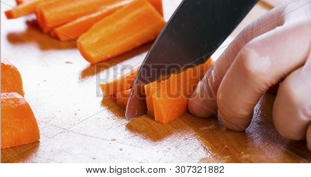 Man Cutting Carrot On Table