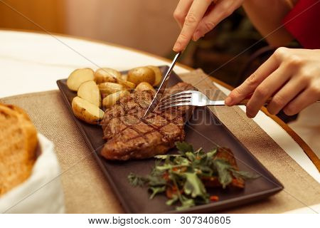 Focus On The Meat Where The Fork And Knife. Beautiful Female Hands In A Restaurant At The Table Cut