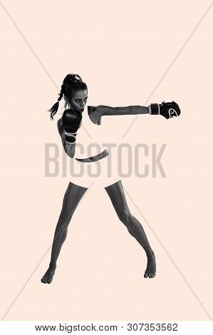 Young Active Beautiful Woman Full Of Energy With The Black Boxing Gloves Training And Practicing At