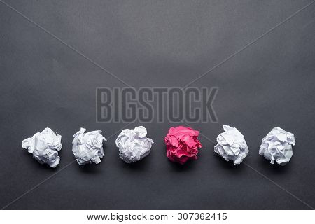 Crumpled Pink Paper Ball Among White Balls On Black Background. Dissimilar Solution Of Problem. Thin