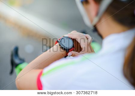 Young Woman Road Cyclist Resting with Bicycle and Using Multisport Smartwatch at Sunset. Closeup of Hands with Fitness Tracker. Training and Sports Concept.