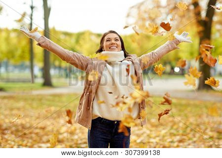 season and people concept - happy young woman throwing maple leaves and having fun in autumn park
