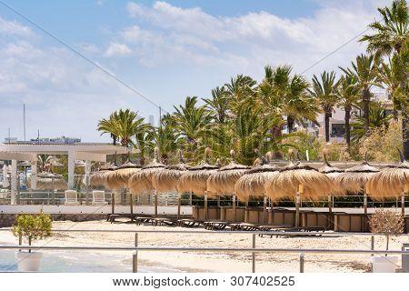 Sandy Beach With Straw Umbrellas In Port De Pollenca (puerto Pollensa). Mallorca. Spain