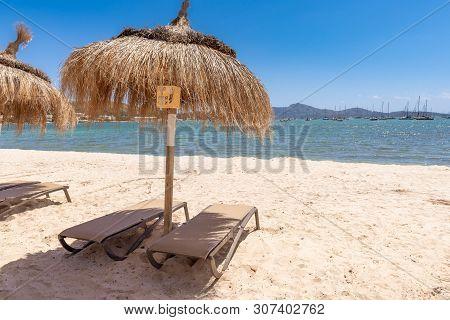 Straw Umbrellas With Sunbeds On The Sandy Beach In Beautiful Port De Pollenca (puerto Pollensa). Mal