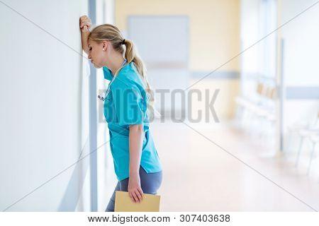 Tired female nurse in hospital corridor