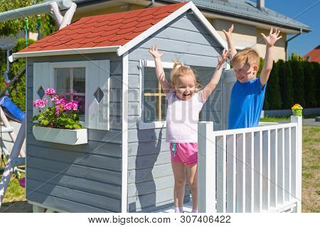Little boy and girl twins at the beautiful garden house