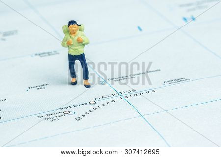 Closeup Of Miniature Figurine Of Young Traveller Standing On Big Map Next To Mauritius