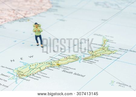 Closeup Of Miniature Figurine Of Young Traveller Standing On Big Map Next To New Zealand Islands
