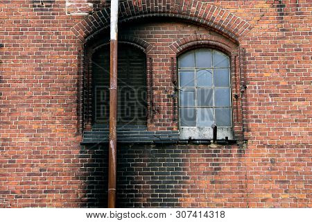 Black Chimney On The Background Of A Brick Wall, Covered In Soot. Inaccurate Behavior With Fire
